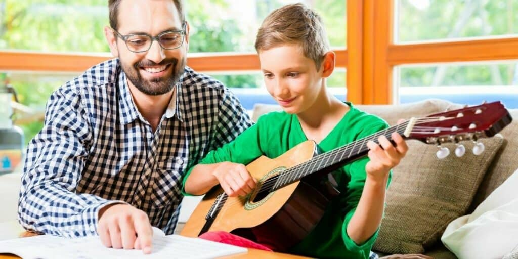 FATHER AND SON LEARNING TO PLAY THE GUITAR